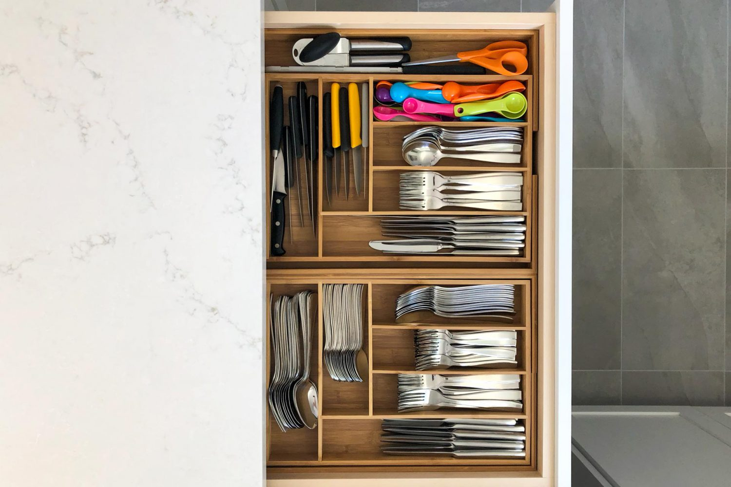 a kitchen drawer is pulled out showing its contents